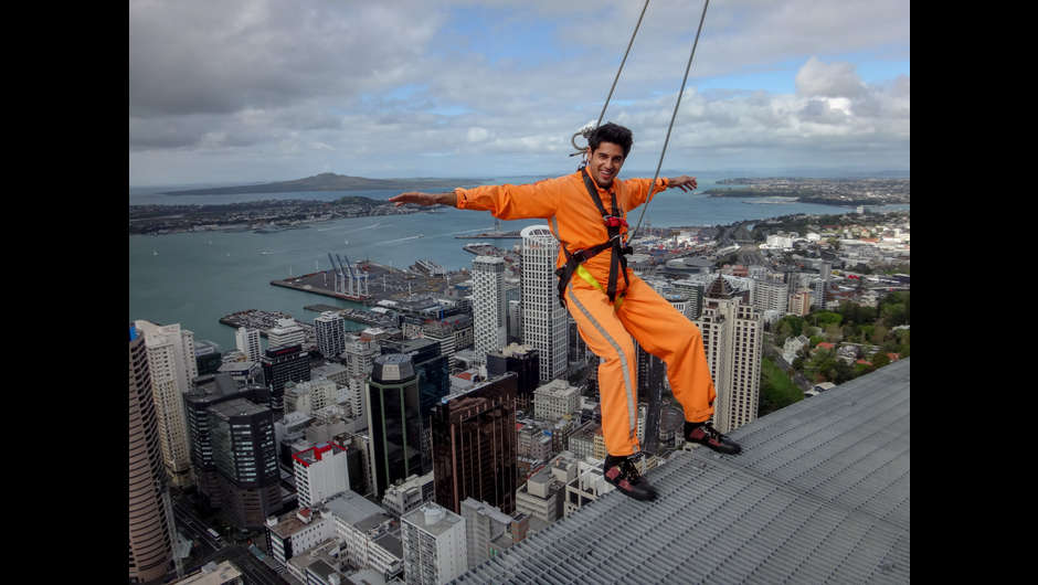 Bollywood superstar Sidharth Malhotra leans out over Auckland City during the Skywalk around the perimeter of the southern hemisphere's tallest building, the Sky Tower.  CREDIT: Camilla Rutherford