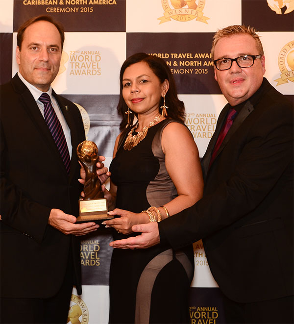 """From left: Mr Michael DiLollo, CEO, Caribbean Airlines and Alicia Cabrera, Senior Marketing Manager, Caribbean Airlines with Chris Frost, Vice President, World Travel Awards upon receiving the award for """"Leading Caribbean Airline""""."""