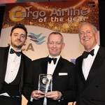 Daniel Parker, Qatar Airways Vice President Global Sales – Cargo (centre) receives the award from Dan Morgan-Evans, Air Charter Service (left).