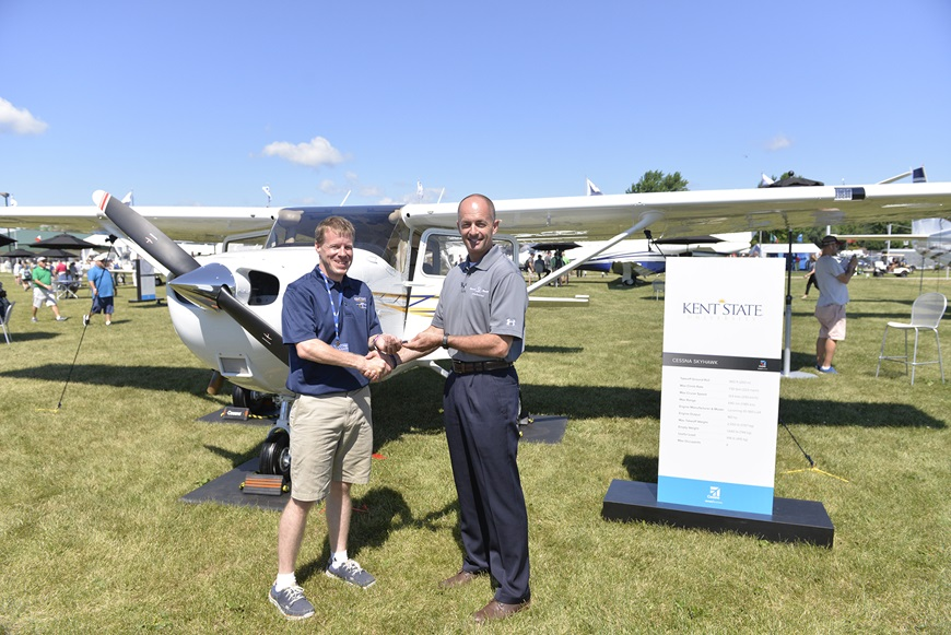Doug May, vice president of Piston Aircraft presents Skyhawk keys to Stephen Pfanner, Kent State University chief flight instructor at Textron Aviation's static display at the Experimental Aircraft Association (EAA) AirVenture.