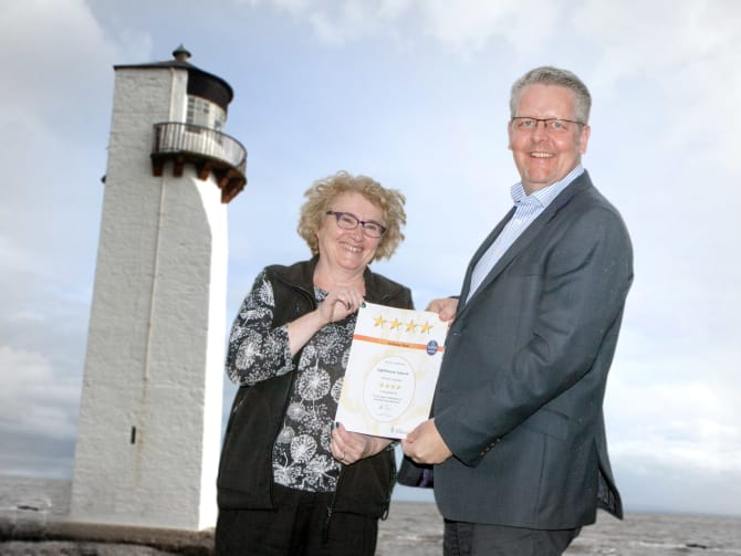 Sylvia Hunt from Lighthouse Leisure Caravan Park accepts the award from VisitScotland Regional Director Doug Wilson