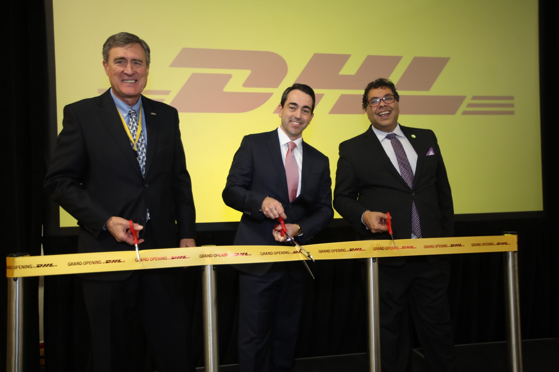 Pictured: Mel Belich, Calgary Airport Authority Board Chair (L) and His Worship Calgary Mayor Naheed Nenshi (R) join Andrew Williams, CEO of DHL Express Canada, in officially opening DHL's expanded cargo facilities at YYC Calgary International Airport.